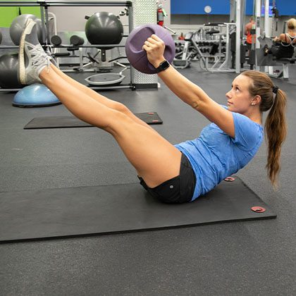 woman working out her core with a workout ball