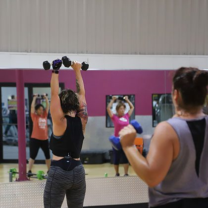 Woman teach a group fitness class, lifting weights.
