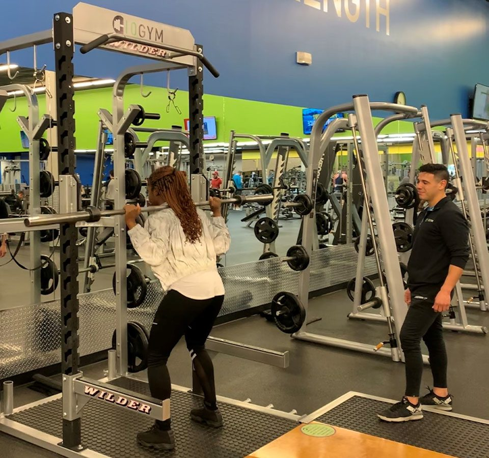 Personal trainer helping a client lift weights.