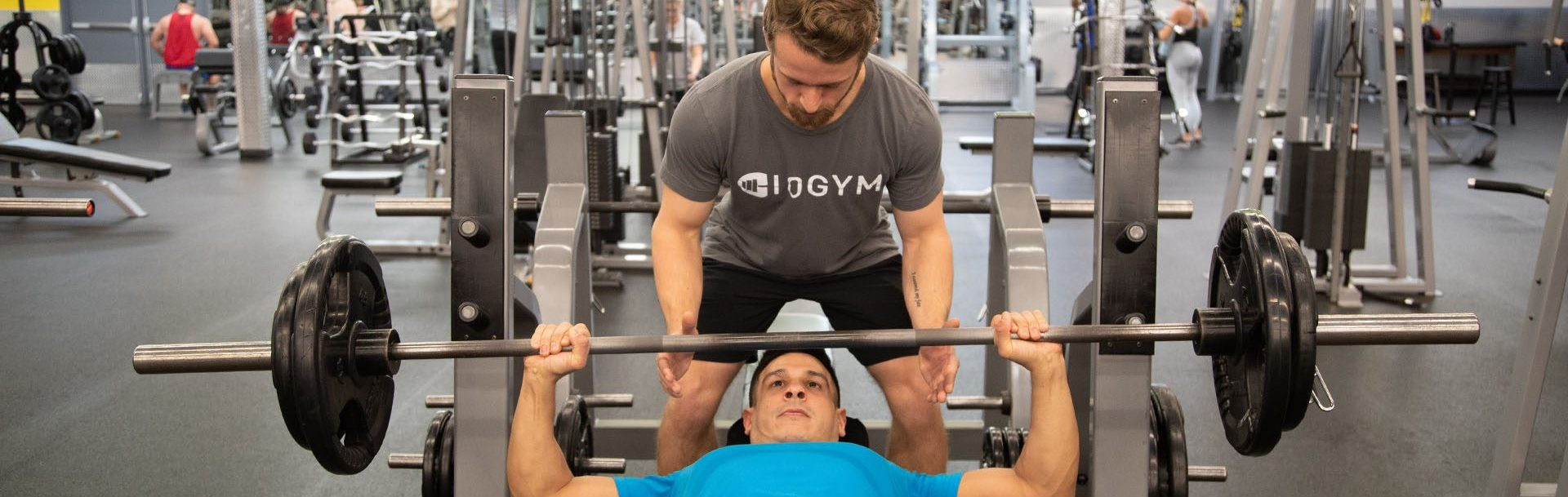 top rated personal trainer helping client lift weights