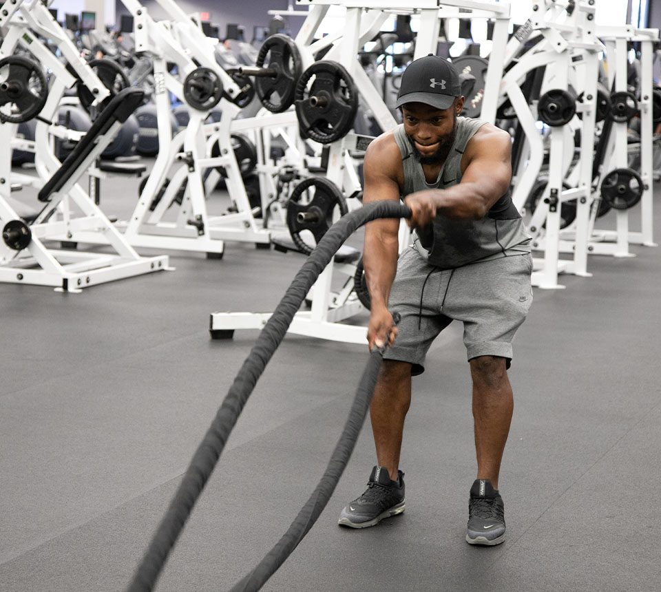Man using battle ropes to workout.